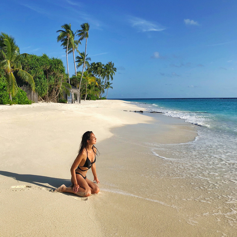 Vivienne Tang on Beach at Velaa Private Island Maldives - Destination Deluxe